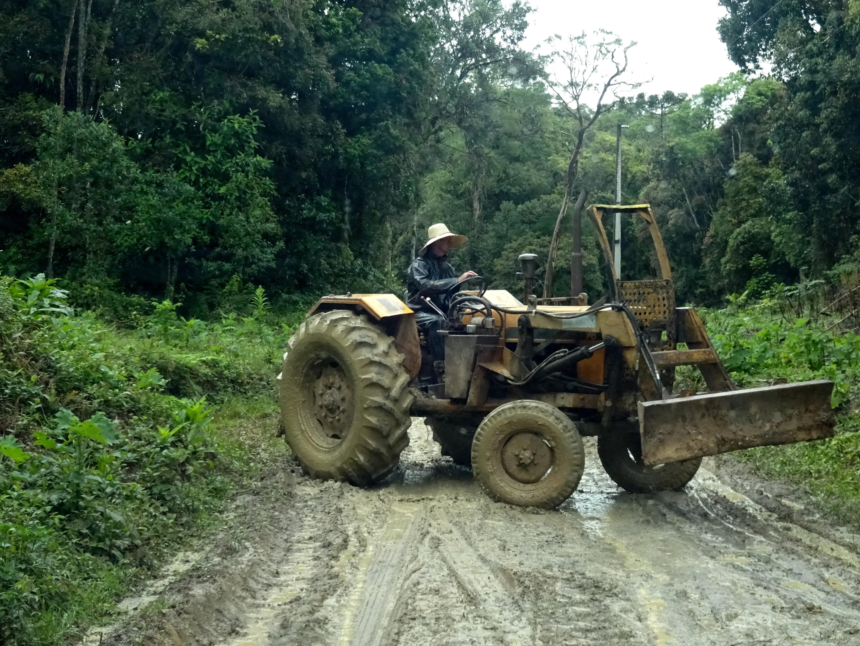 Manden med hat og bare tæer på sin traktor